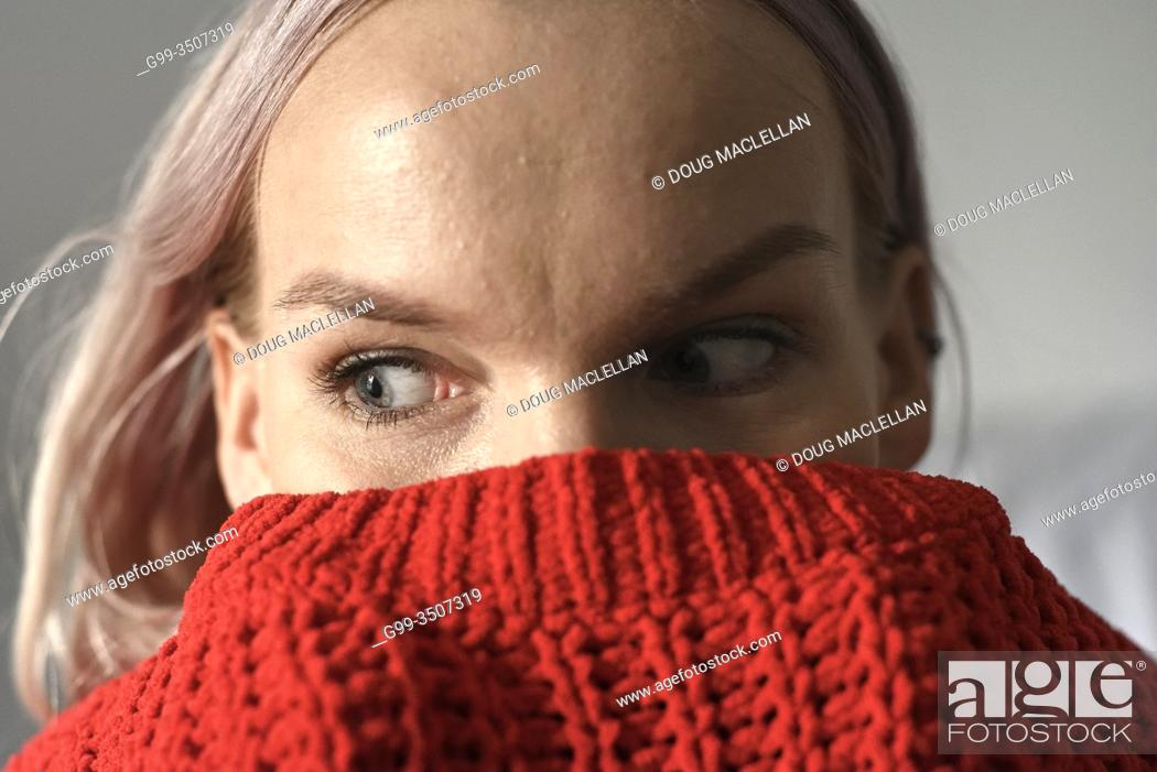 Stock Photo: A woman with light pink hair posing with a red sweater up to her eyes in the autumn in Canada.