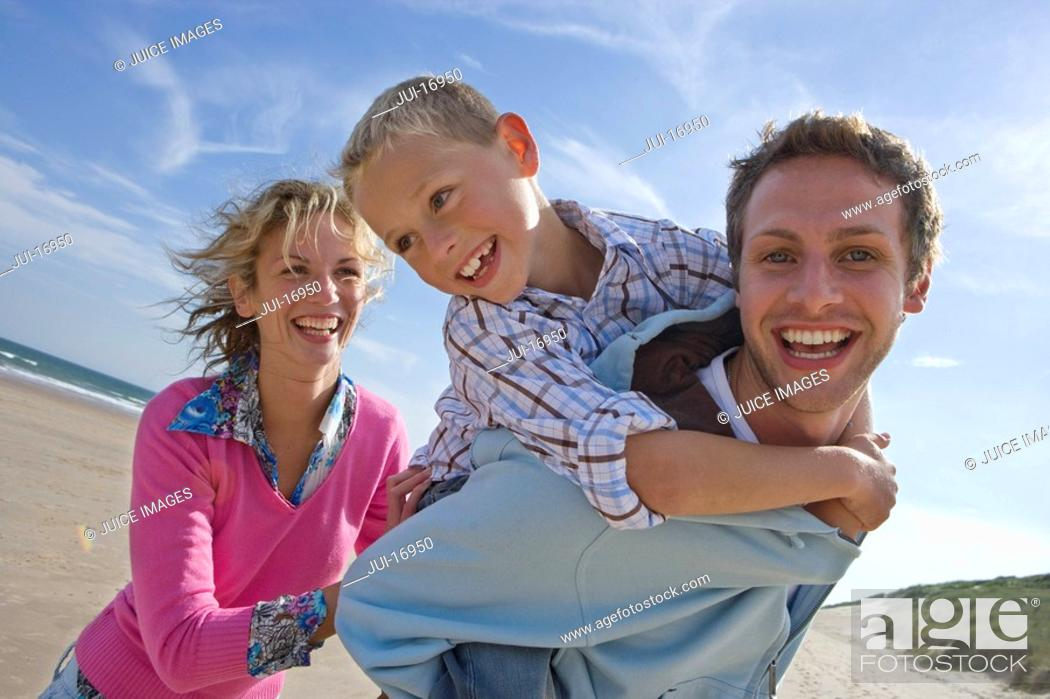 Stock Photo: Father piggybacking son on beach, mother in background.