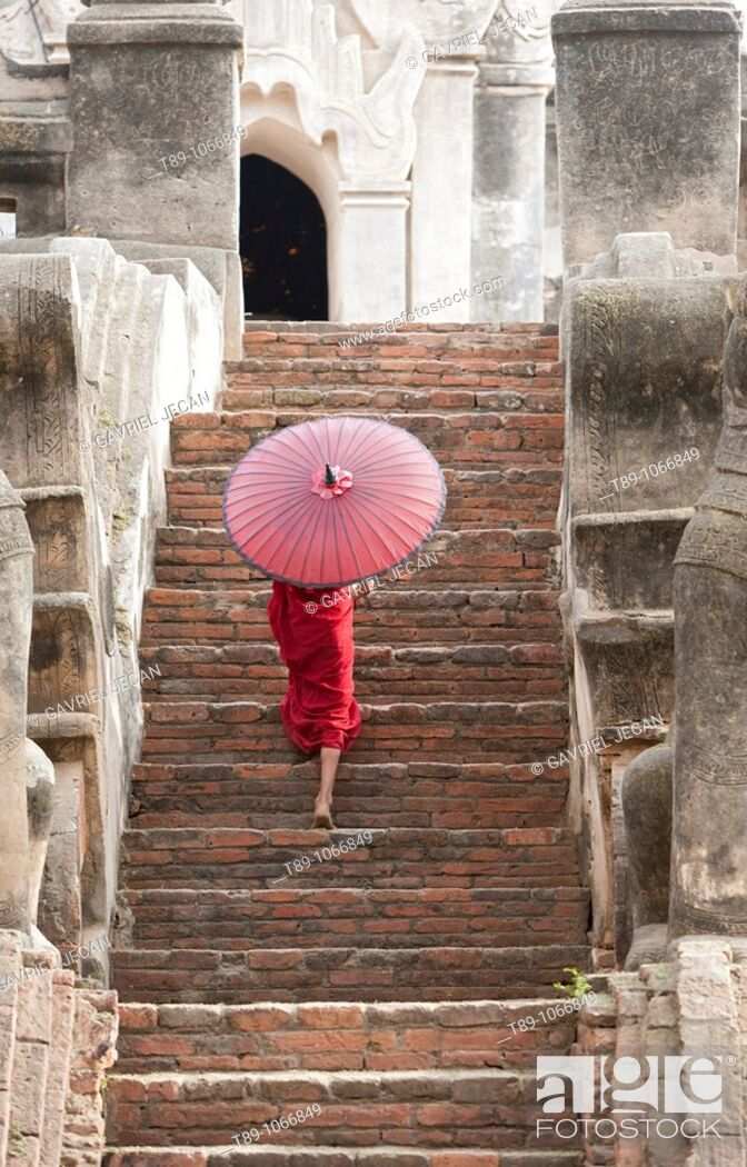Stock Photo: Young monk walking with umbrela.