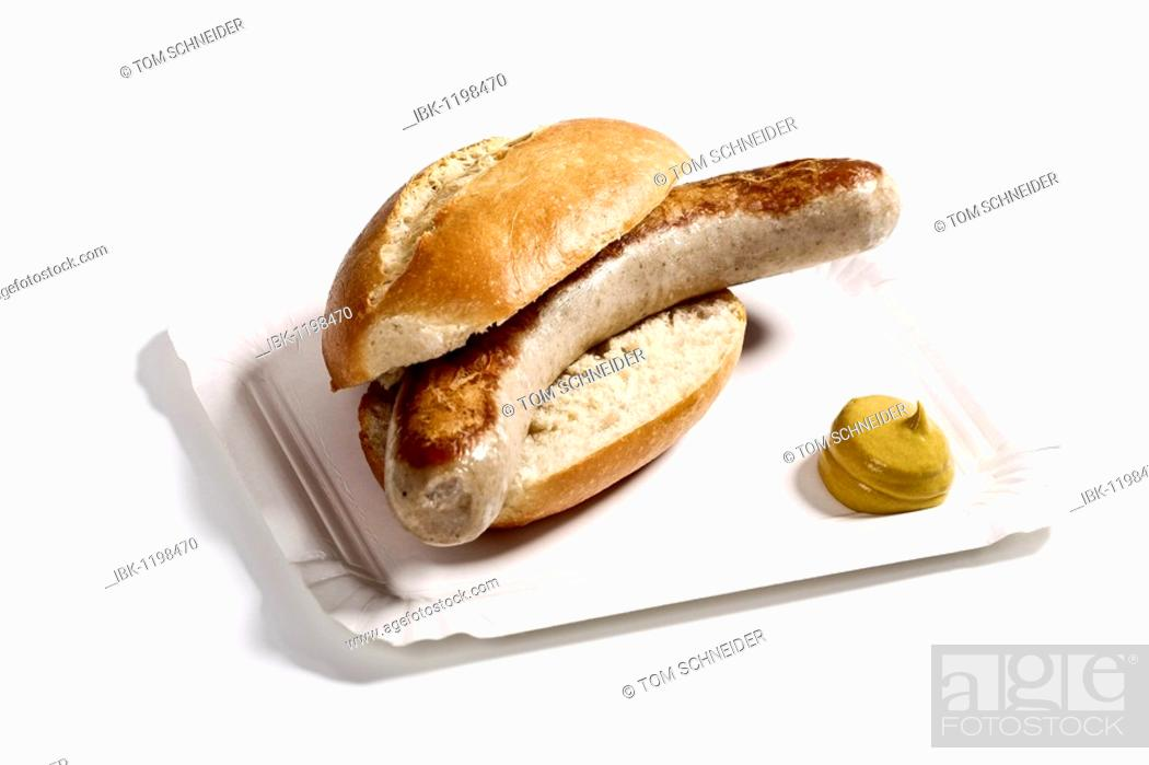 Stock Photo: Bratwurst sausage in a bun with mustard on a paper plate.