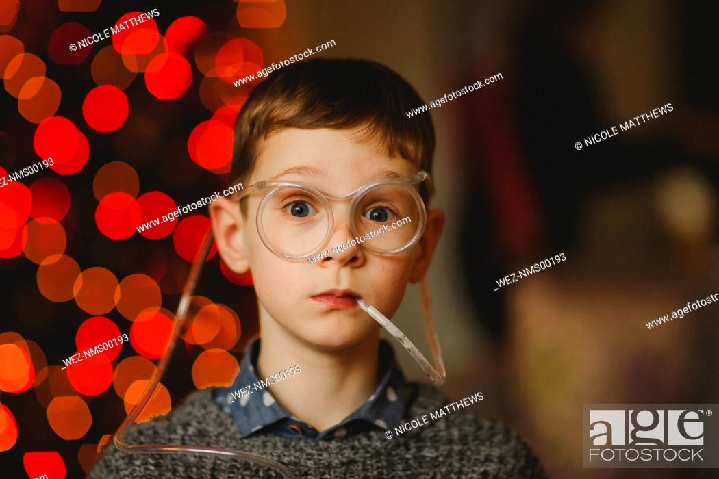 Imagen: Portrait of boy wearing funny glasses with drinking straw.