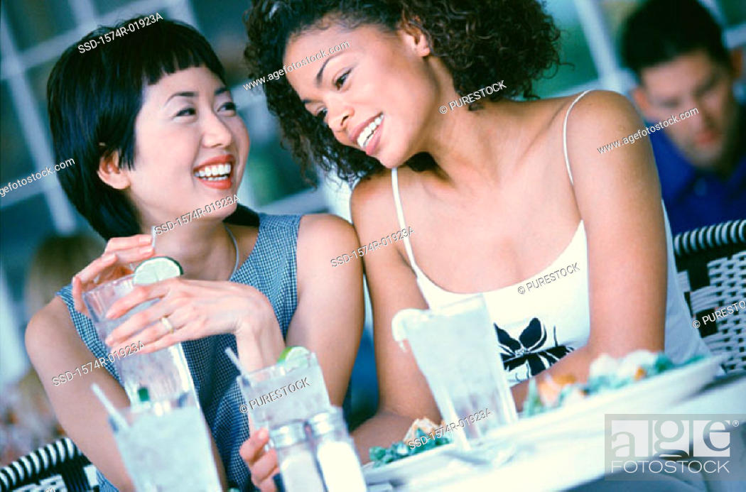Stock Photo: Two young woman seated at a table smiling.