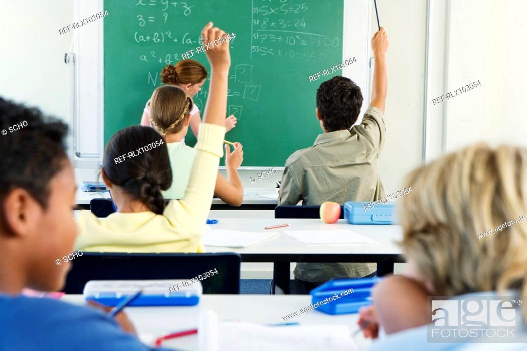 Stock Photo: Group of school children 10-13 in classroom with hands raised.