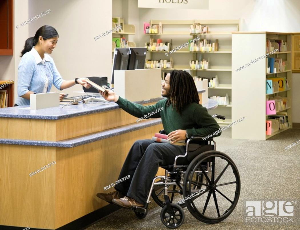 Stock Photo: African man in wheelchair at library.