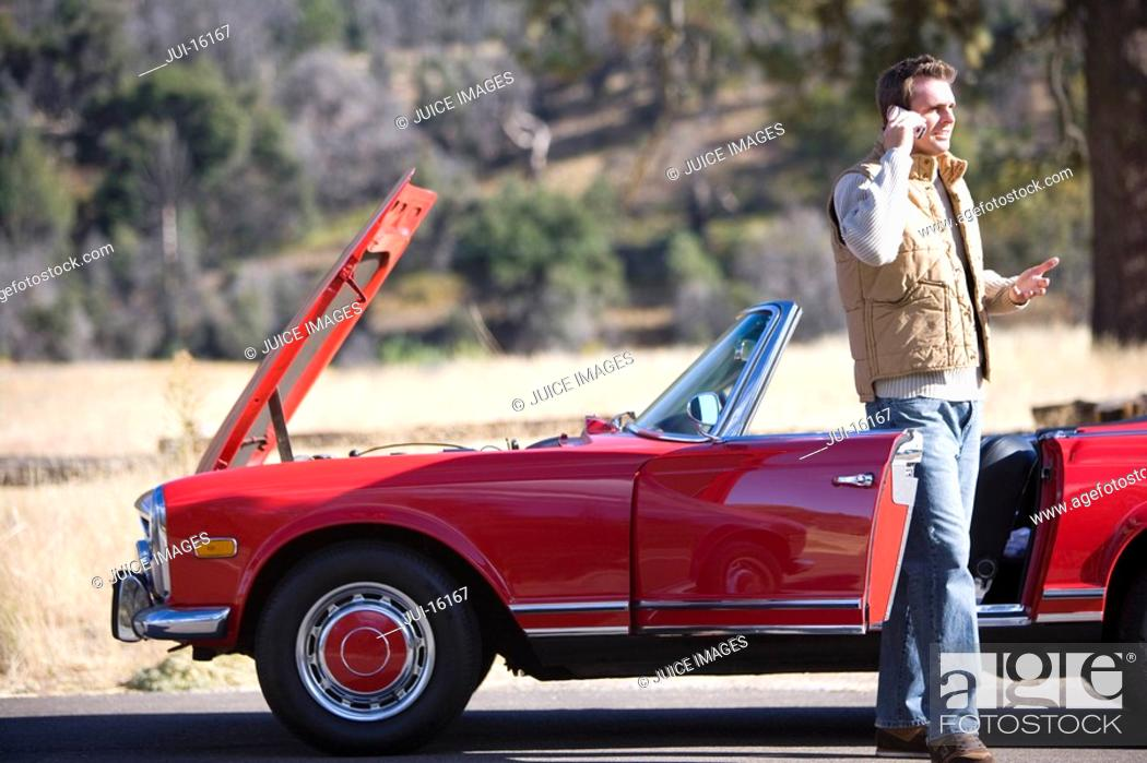 Stock Photo: Man talking on cell phone next to broken down red convertible.