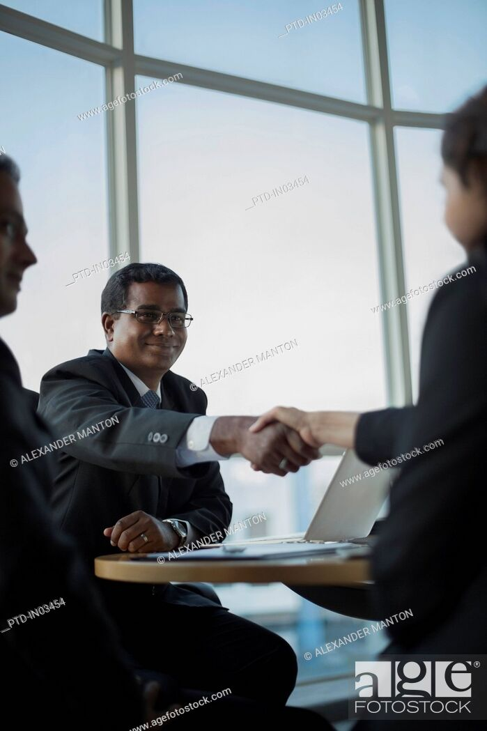 Stock Photo: Singapore, Man looking at businessman shaking hands with woman.