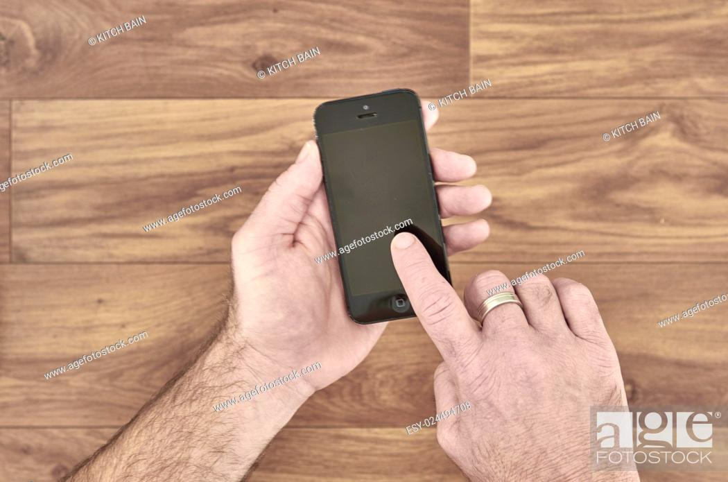 Stock Photo: A studio photo of a mobile phone in hand.