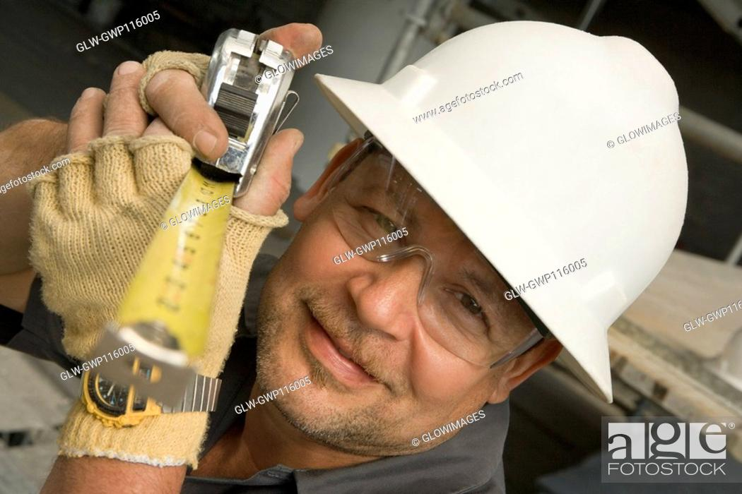 Stock Photo: Close-up of a male construction worker holding a tape measure.