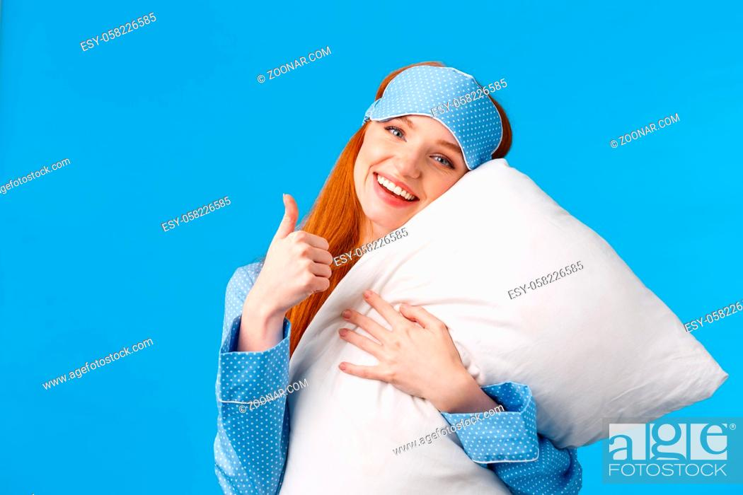 Stock Photo: Saying yes to good healthy sleep. Cheerful pretty redhead woman in sleep mask and nightwear, hugging soft pillow showing thumbs-up in approval, like gesture.