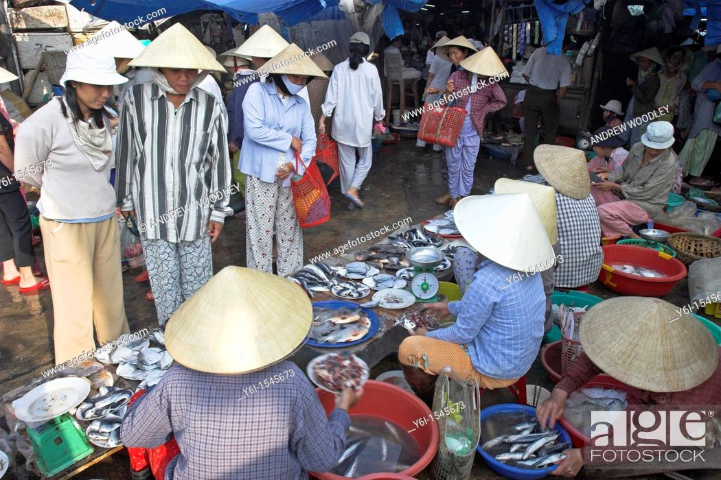 Stock Photo: Women in conical hats buy and ssell fish at riverside market Hoi An historic town mid Vietnam.