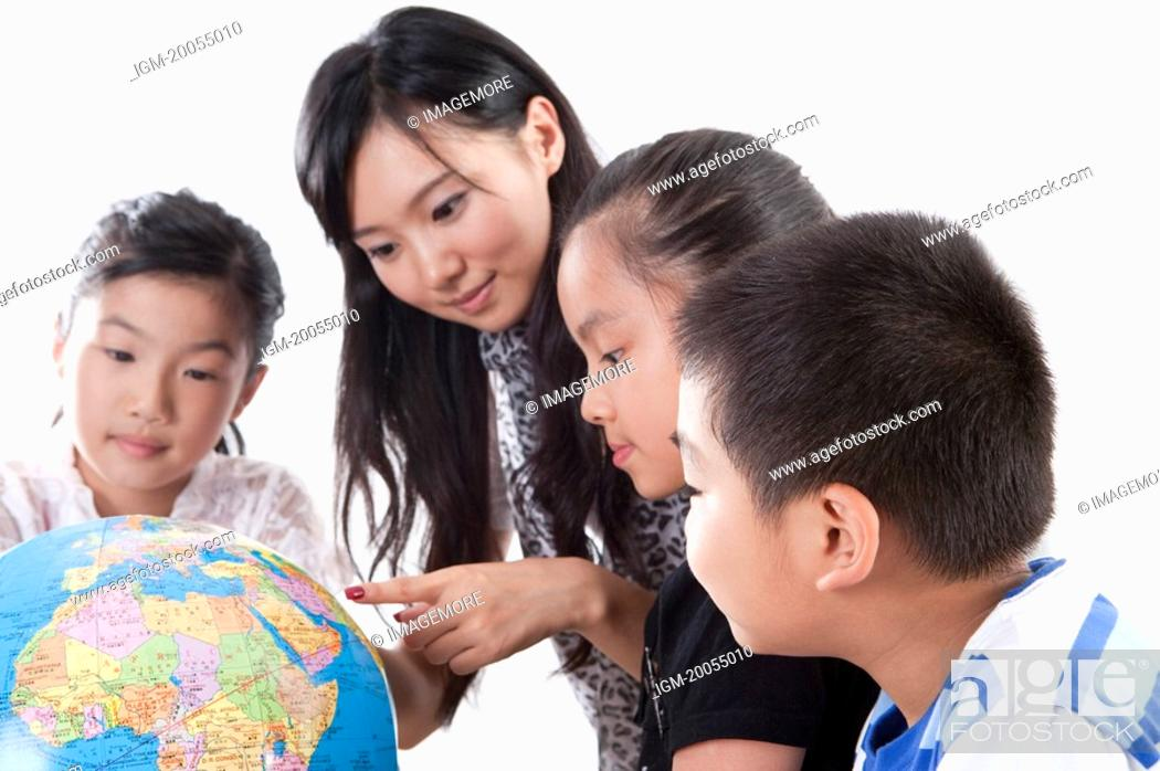 Stock Photo: Child, Young teacher and students looking at the globe together.