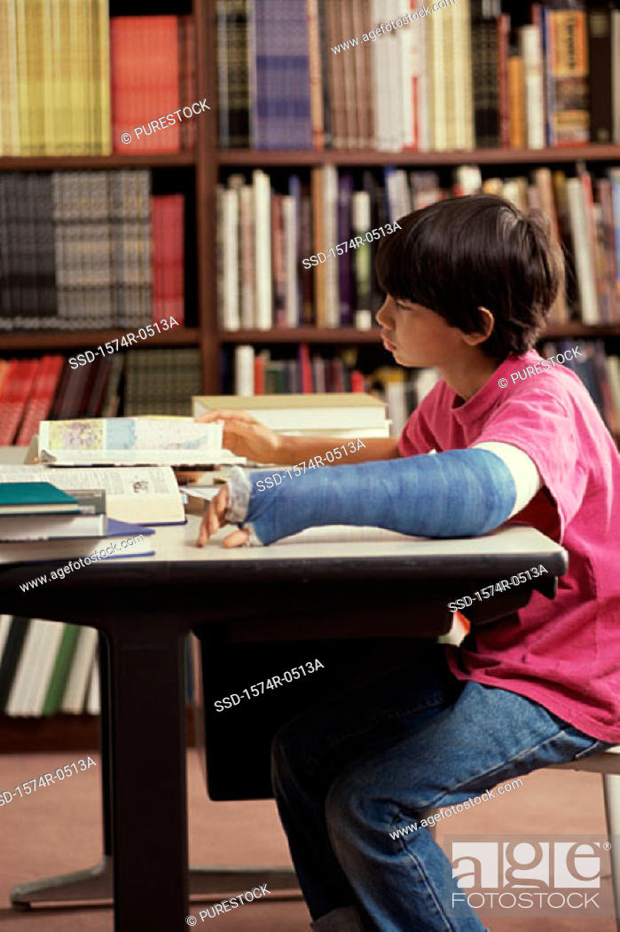 Stock Photo: Boy sitting in a library and studying.