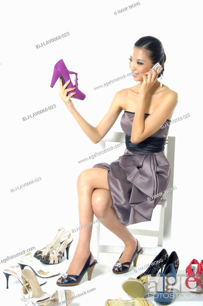 Stock Photo: Woman looking at a shoe and talking on a mobile phone.