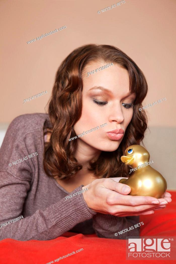 Stock Photo: Young woman holding a rubber duck in bed.