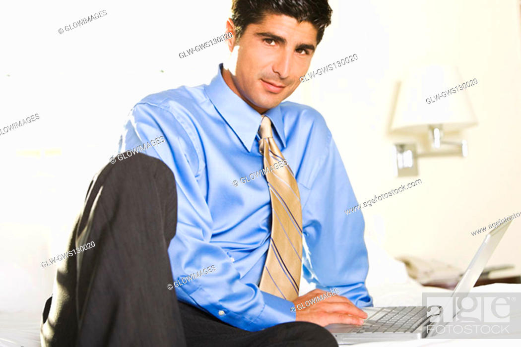 Stock Photo: Portrait of a businessman working on a laptop.