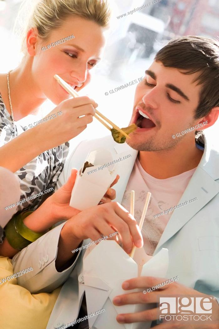 Stock Photo: Young woman feeding food to a young man.