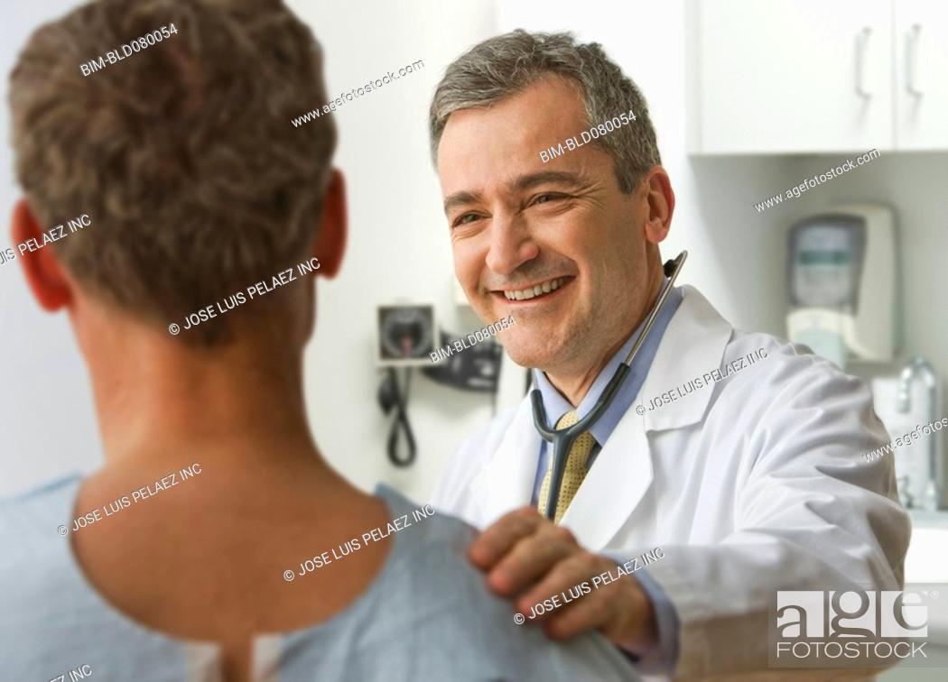 Stock Photo: Doctor talking to patient in examination room.