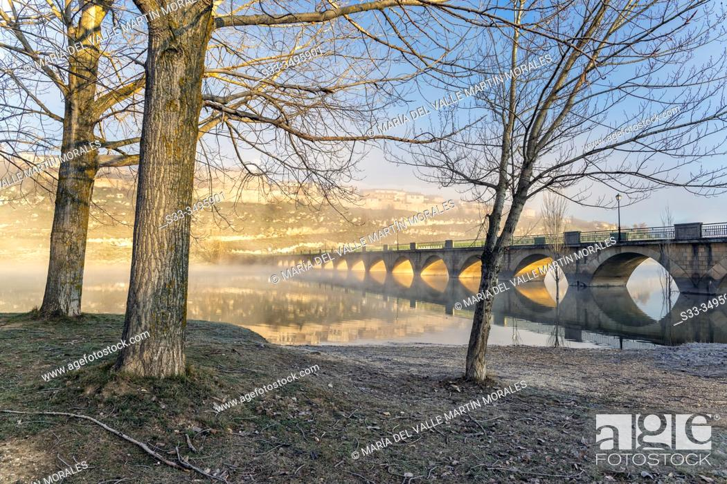 Photo de stock: Long bridge over The Linares del Arroyo reservoir and Maderuelo village on a foggy morning. Segovia. Spain. Europe.