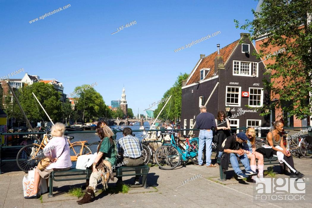 Stock Photo: People, de Sluyswacht, Oude Schans, People sitting on bridge in the near of de Sluyswacht, a typical brown cafe at canal Oude Schans, Amsterdam, Holland.