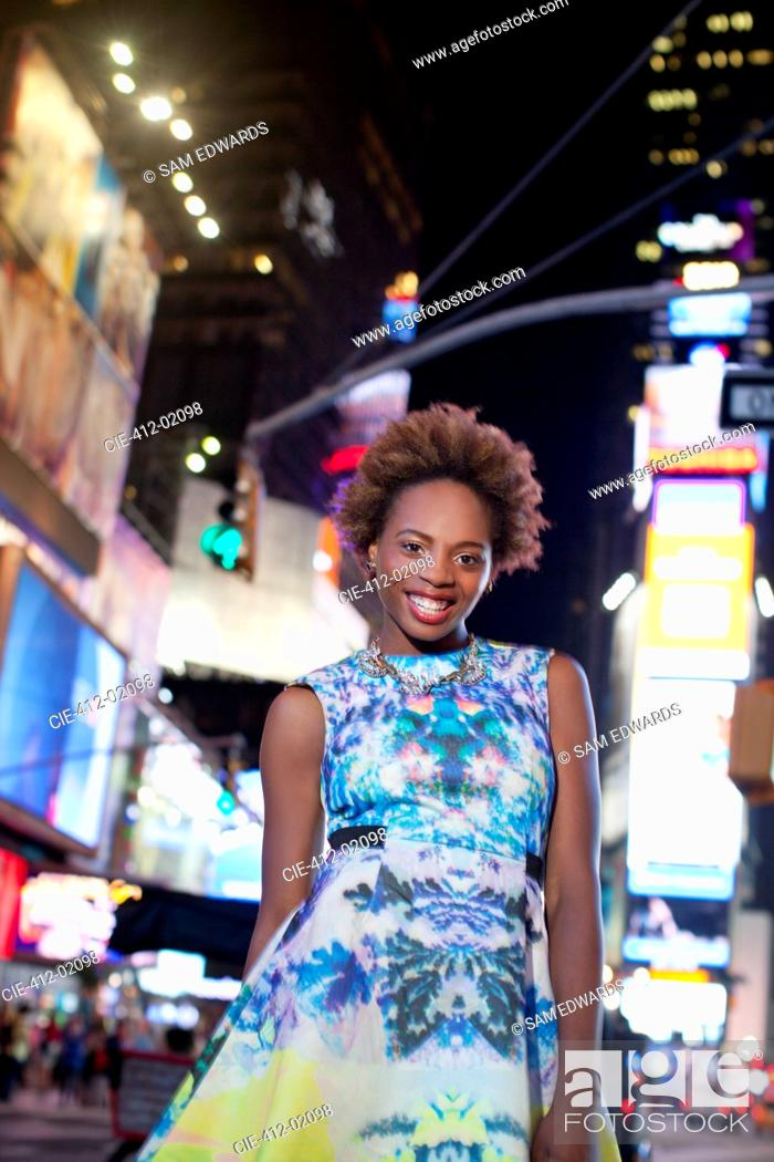 Stock Photo: Woman standing on city street at night.
