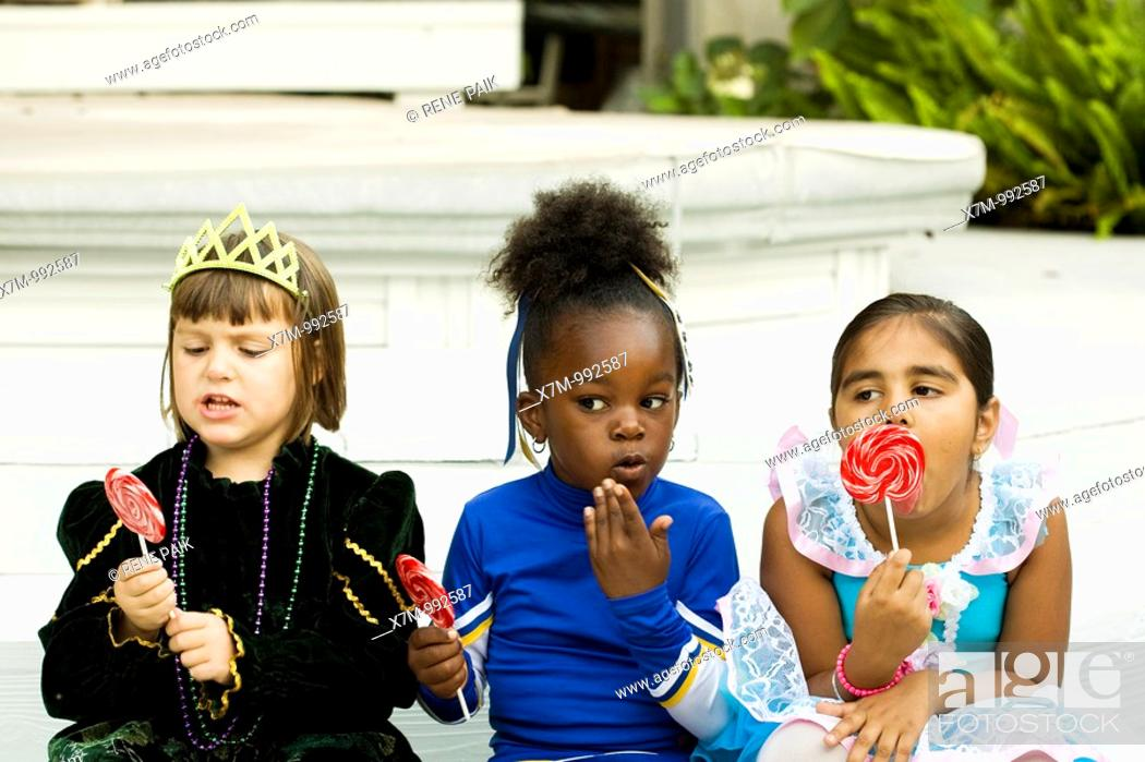 Stock Photo: Little girls Asian Indian, black & caucasian dressed in Halloween costumes enjoy their lollipops as one gets caught red-handed eating candy.