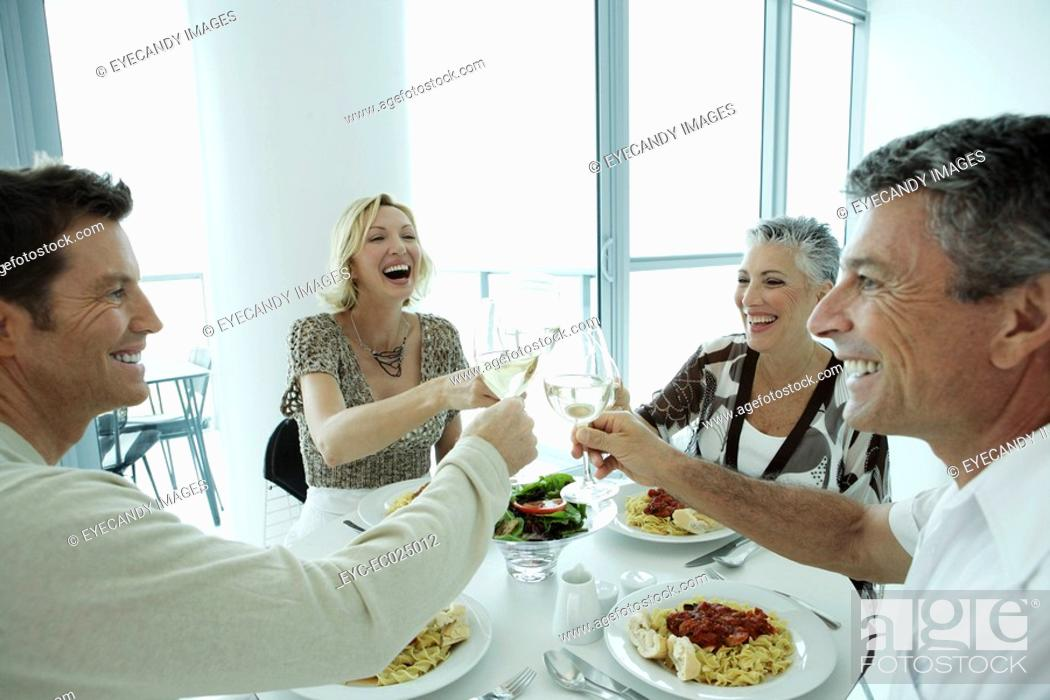 Stock Photo: View of four people toasting glasses.