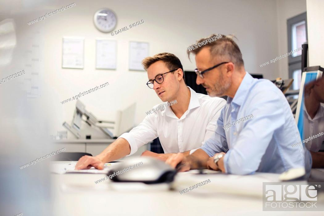 Stock Photo: Two businessmen discussing plan on desk in office.