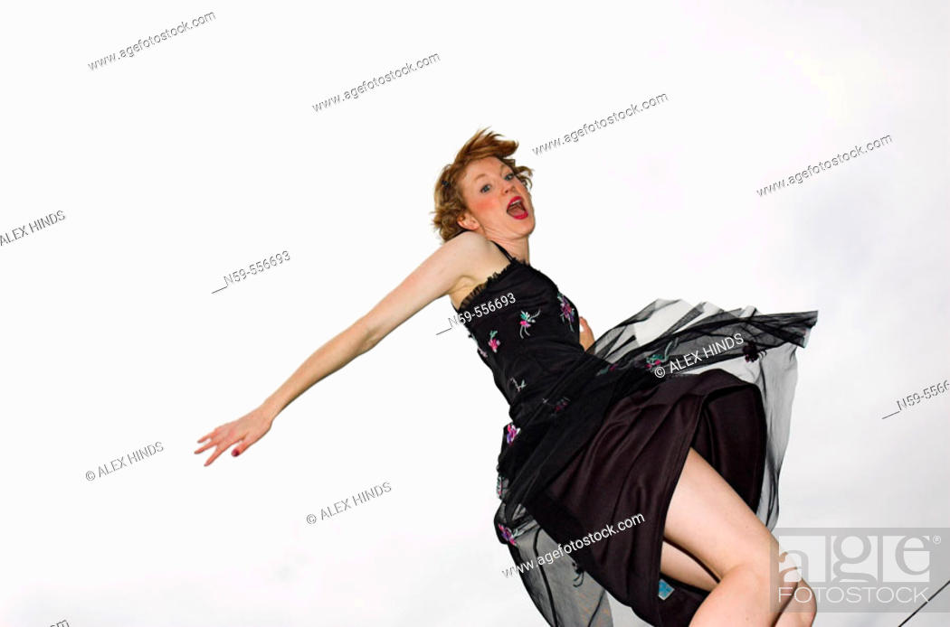 Stock Photo: Girl in party dress jumping with excitement.