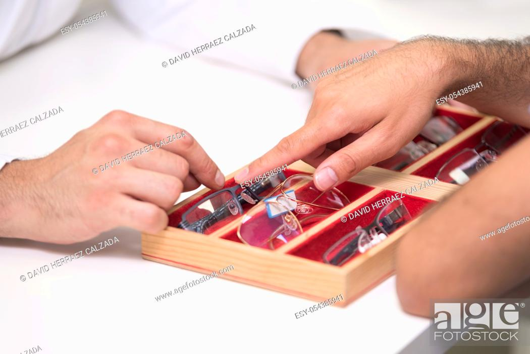 Stock Photo: ophthalmologist hands close up, showing a tray with different glasses to a customer .