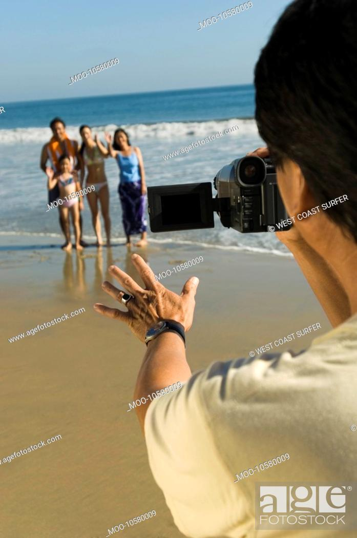 Stock Photo: Man filming family on beach.