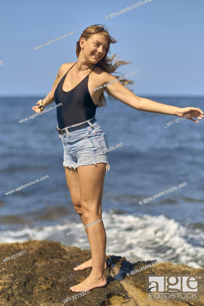 Stock Photo: young woman stretching arms in wind at seaside, enjoying summer holiday and freedom, in Crete, Greece.