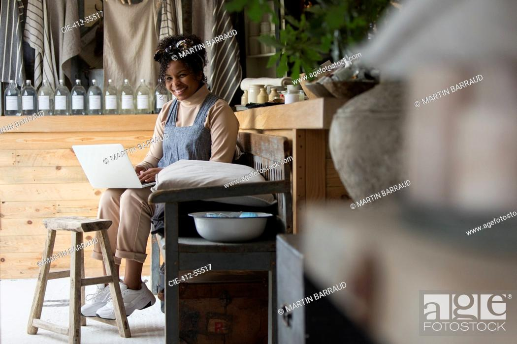 Stock Photo: Portrait happy female shop owner using laptop in home goods store.