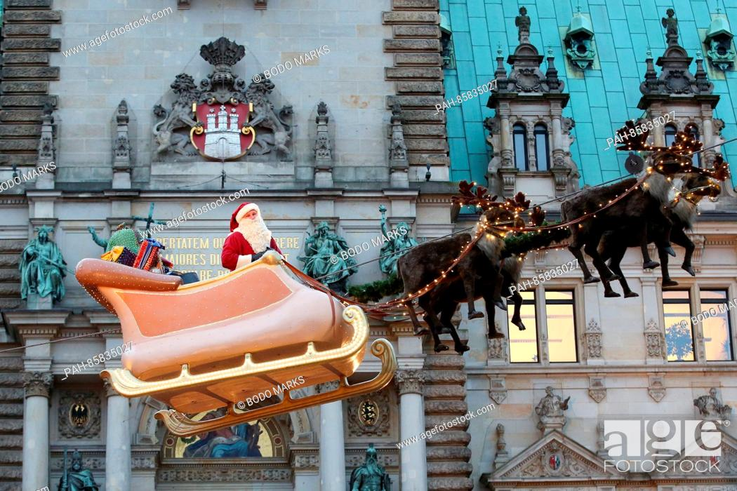 Stock Photo: A Santa Claus impersonator stands on a hovering sleigh at the Historical Christmas Market outside of city hall in Hamburg,Germany, 21 November 2016.