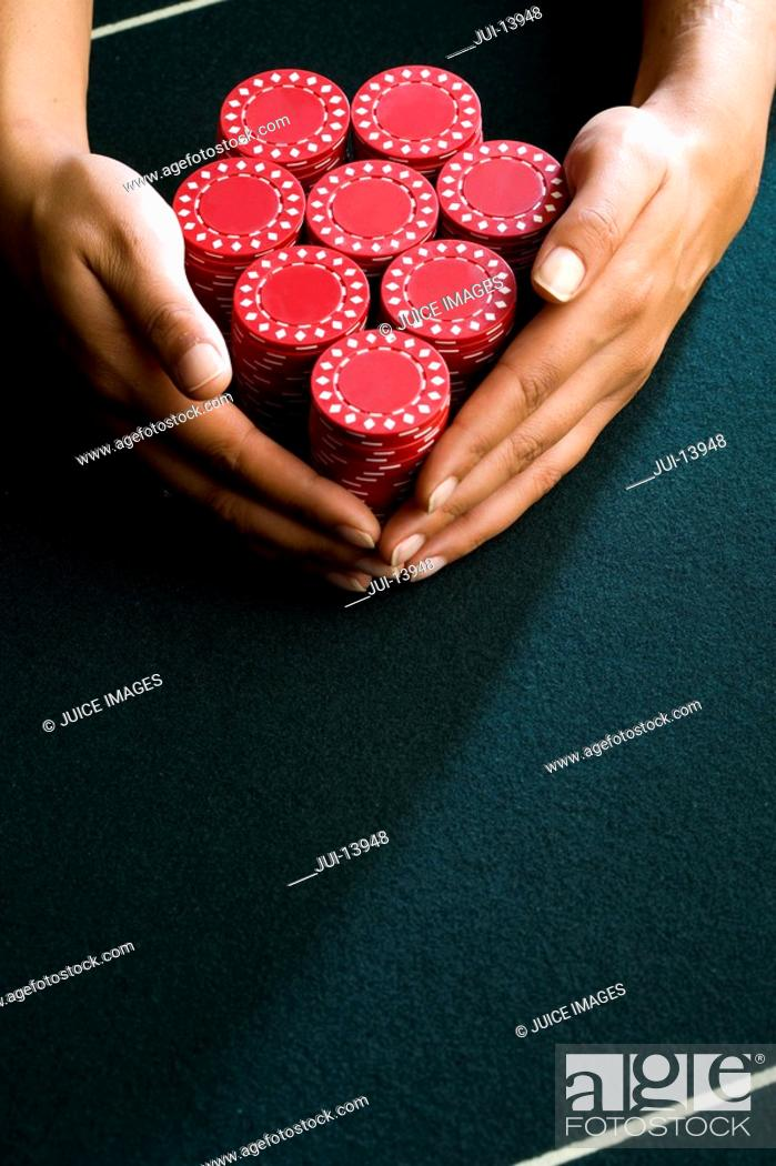 Stock Photo: Woman with hands around piles of gambling chips on table, close-up.