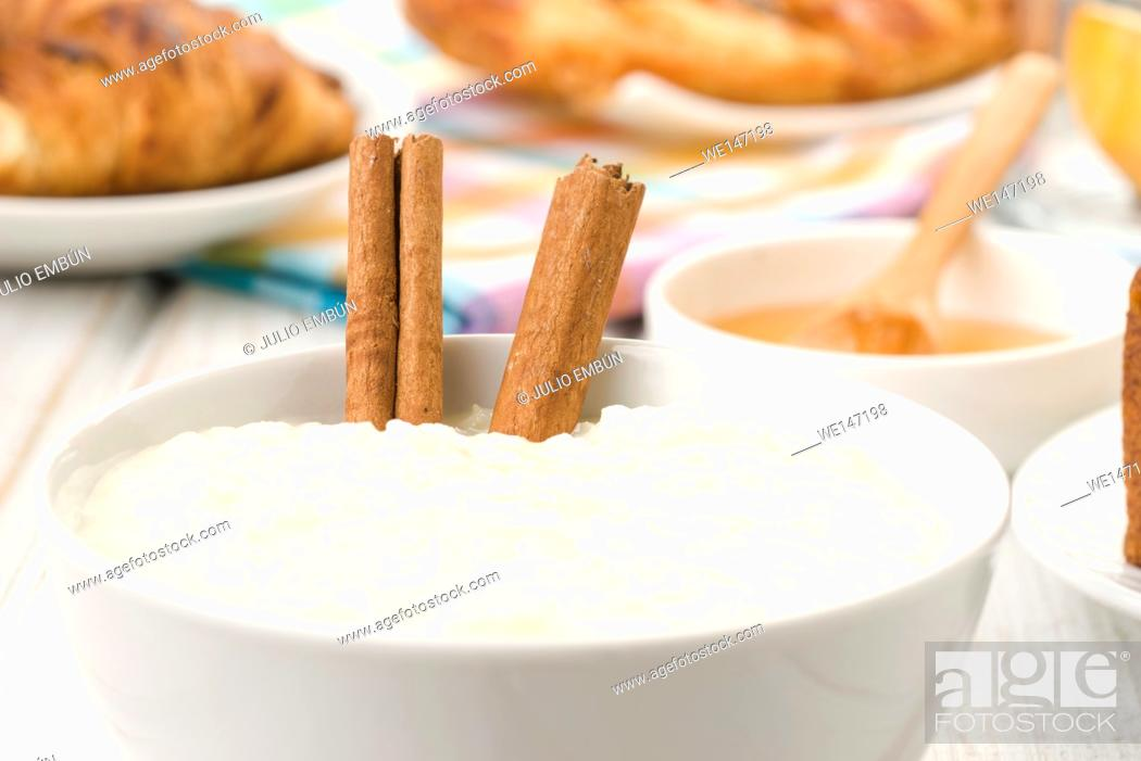 Photo de stock: cinnamon sticks dipped in rice pudding, on white wood.