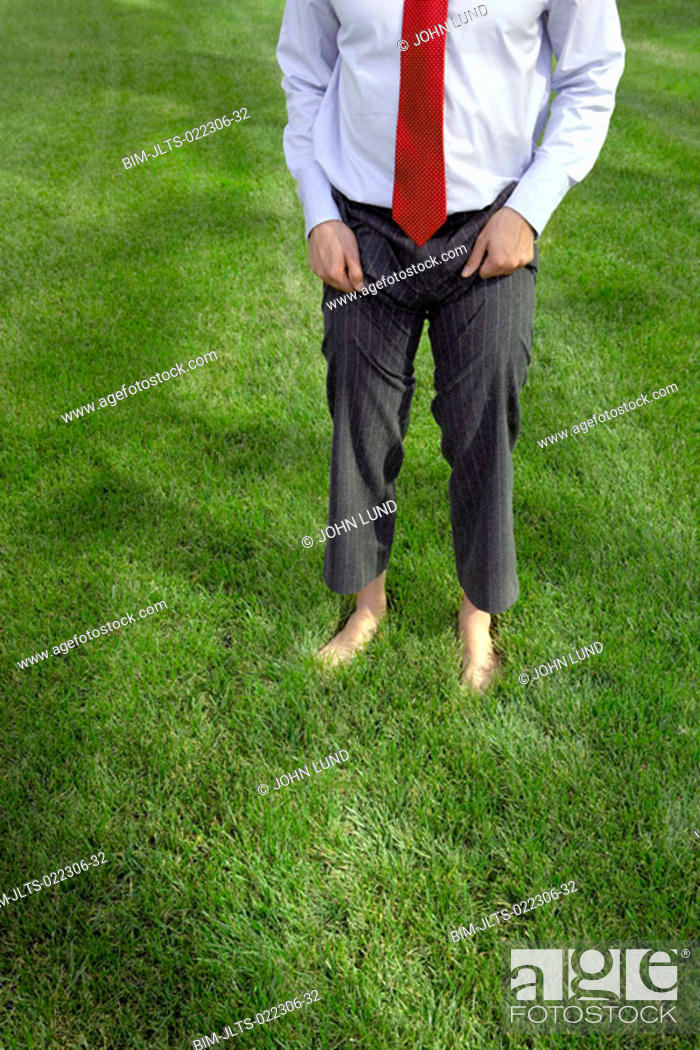 Stock Photo: Businessman standing barefoot in the grass, Redwood City, California, United States.