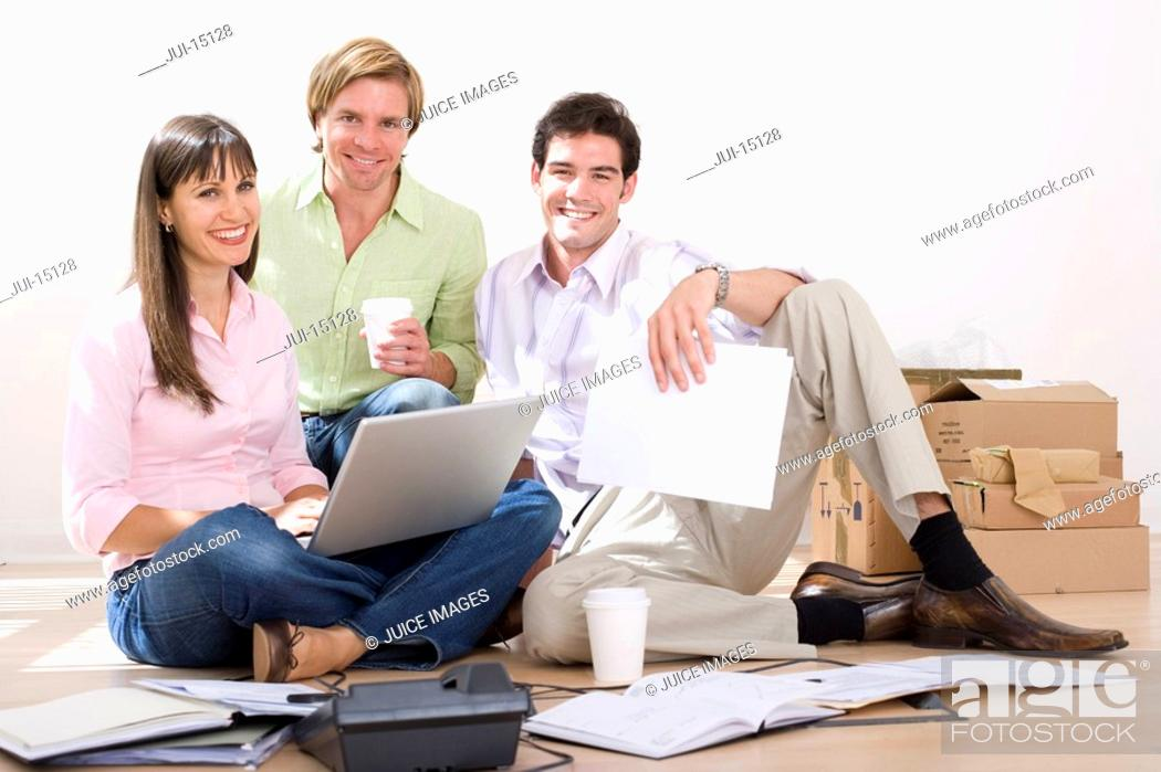 Stock Photo: Woman with laptop by colleagues on floor by boxes, portrait.