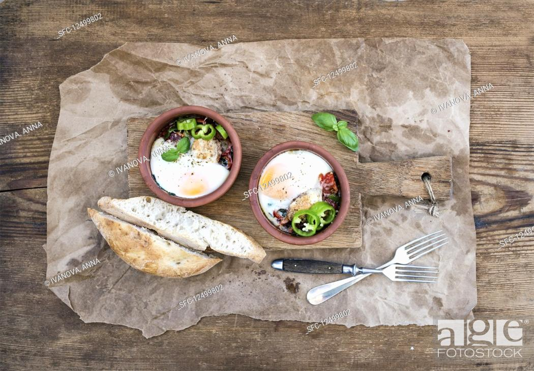 Stock Photo: Country style breakfast - Eggs baked in clay cups with tomatoes, peppers, fresh basil and bread slices.