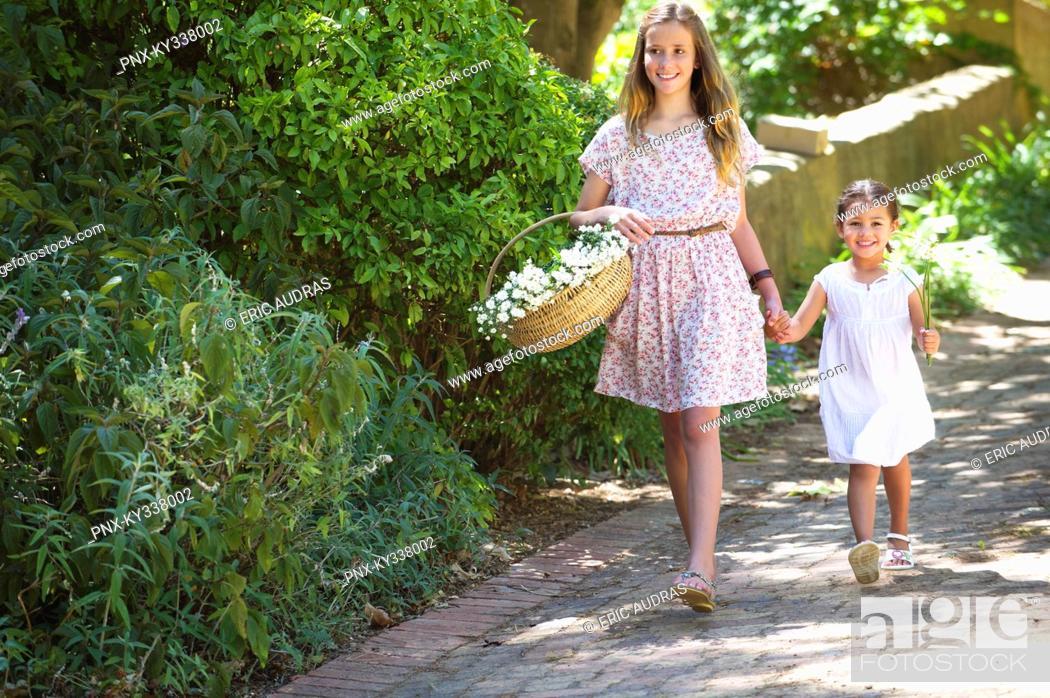 Stock Photo: Happy siblings walking holding hands in garden.