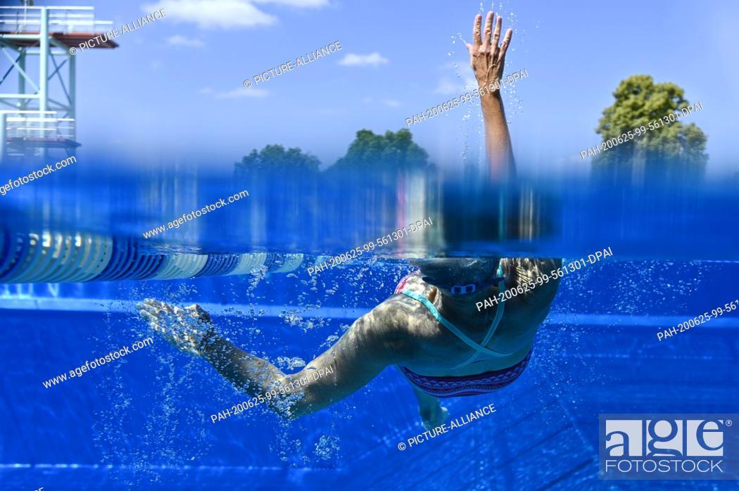 Stock Photo: 25 June 2020, Baden-Wuerttemberg, Heidelberg: A female swimmer draws her lanes in the Tiergarten outdoor pool. Photo: Uwe Anspach/dpa.