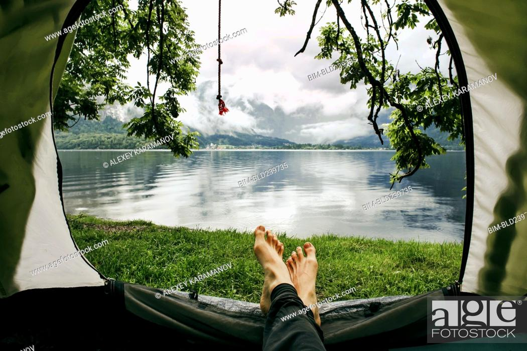 Stock Photo: Feet on man laying in camping tent at lake.