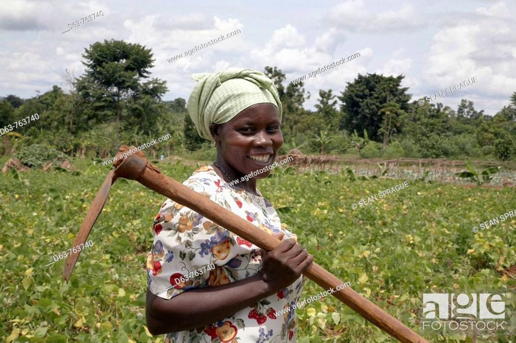 Stock Photo: UGANDA  Nejjemba Teopista, farmer of Kayunga and farmer's group animator, holding her hoe after working in a communal garden at Kangulumira where food is grown.