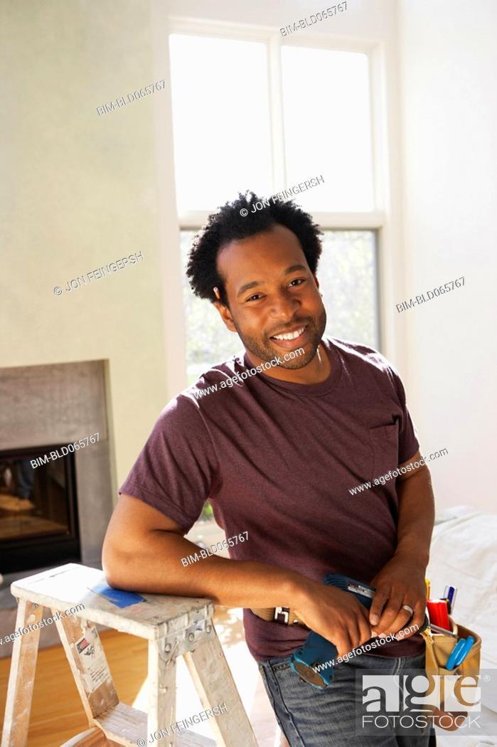 Stock Photo: African carpenter in livingroom.