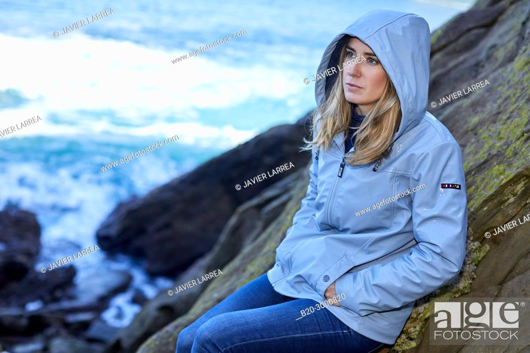 Stock Photo: Adult woman at the coast of Santa Clara Island, Donostia, San Sebastian, Gipuzkoa, Basque Country, Spain, Europe, Raincoat, Winter.