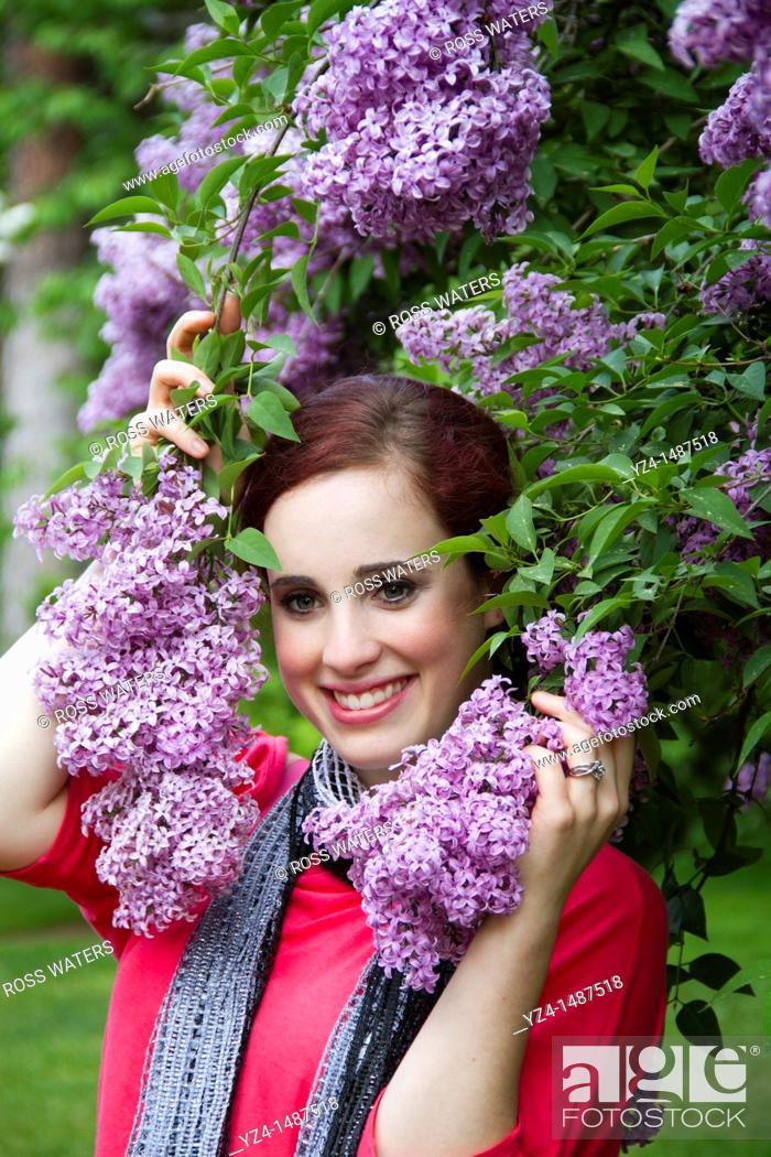 Stock Photo: A young woman with lilacs in Spokane, Washington, USA.