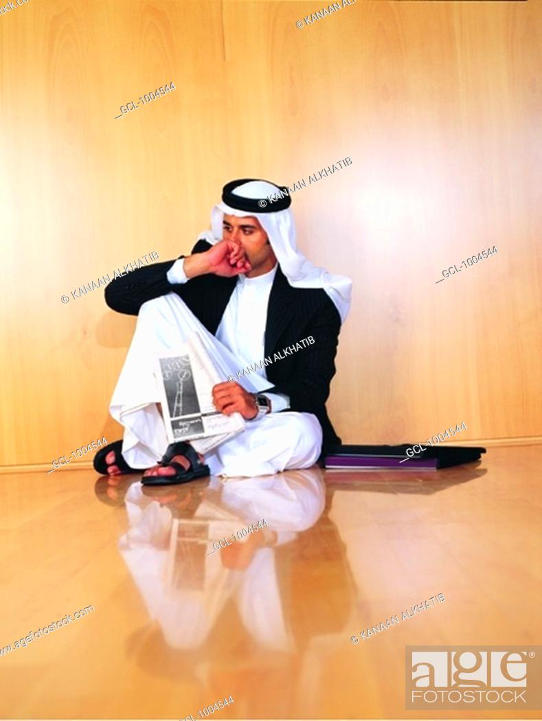 Stock Photo: Saudi Arabian businessman sitting on office floor.