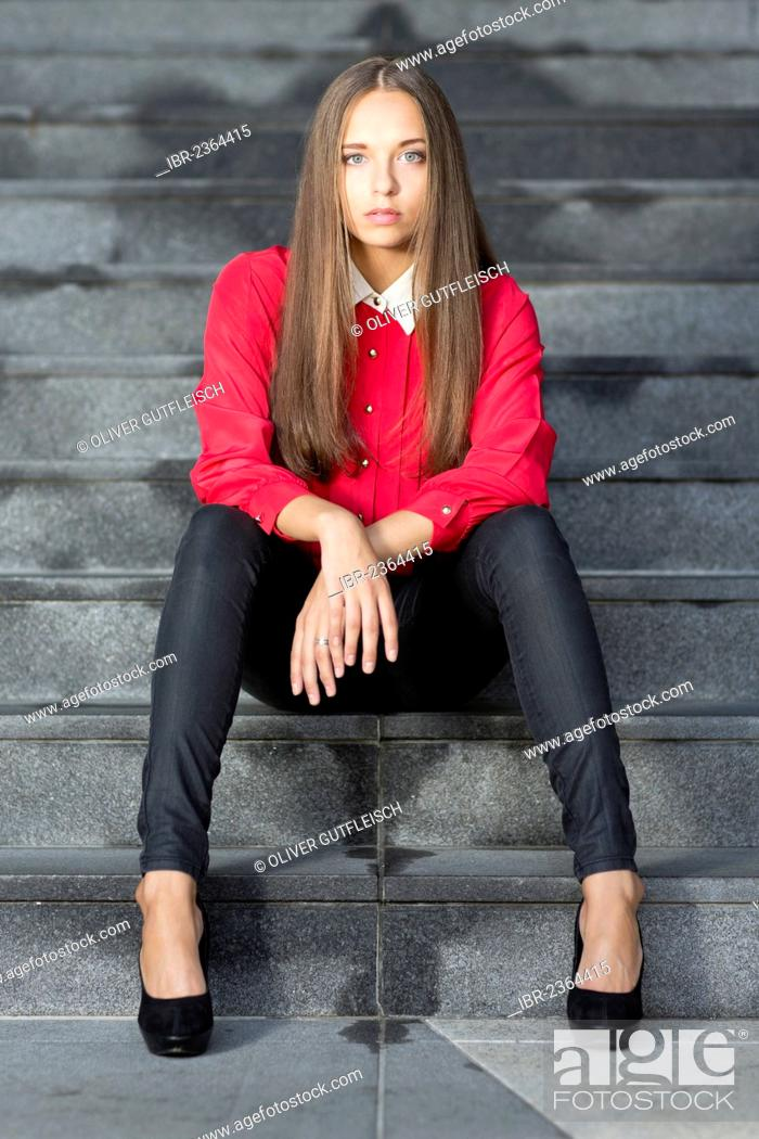 84cb4428c13 Stock Photo - Young woman wearing a red top