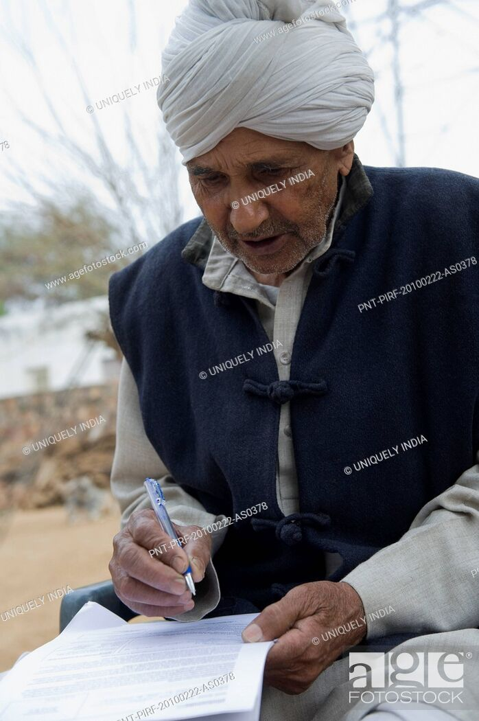 Stock Photo: Farmer signing a document, Hasanpur, Haryana, India.