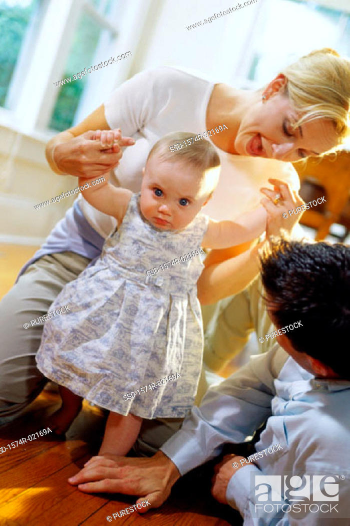 Stock Photo: Parents helping their baby girl learn how to walk.