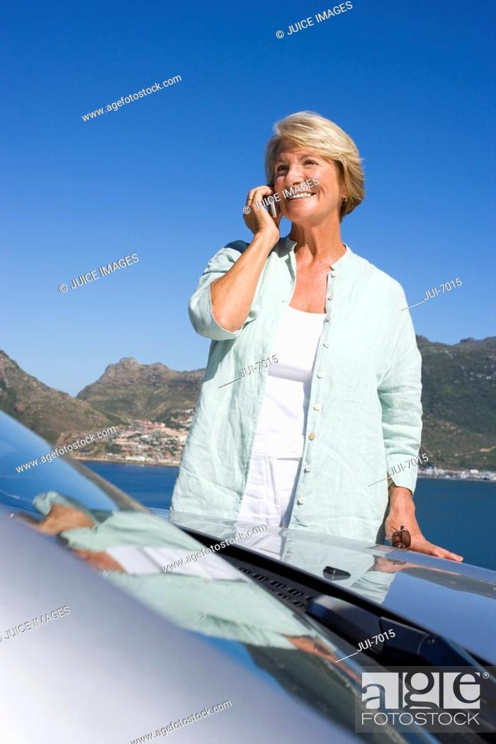 Stock Photo: Senior woman standing beside parked convertible car on clifftop overlooking bay, using mobile phone, smiling.